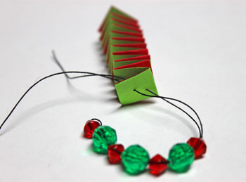 Catstep Braid and Bead Ornament step 13 push thread through holes in end of paper