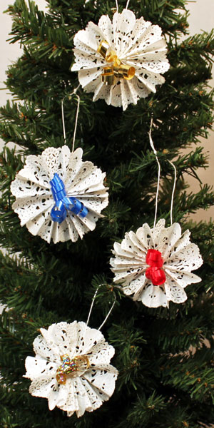 Four Paper Doily Flower Ornaments hanging on a tree