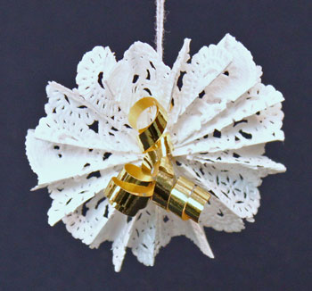 An up close view of a finished paper doily flower ornament in our Easy Christmas Crafts series