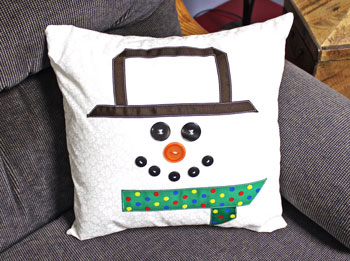Fred the Snowman Pillow finished on couch to the right