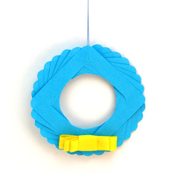 Eight Squares Wreath Ornament blue with yellow bow on display