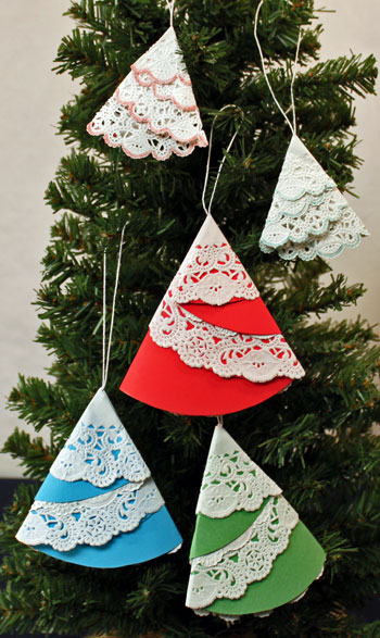 Easy Christmas Crafts Paper Doily Folded Christmas Tree Ornament showing five finished and hanging on tree