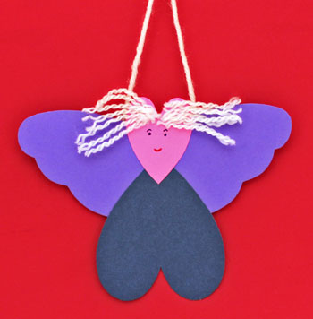 Heart Angel Ornament finished and hanging against a red background